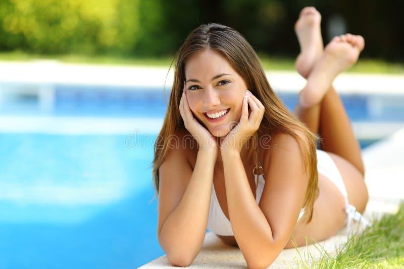 Muchacha feliz que presenta el bikini que lleva en un lado de la piscina en vacaciones de verano imágenes de archivo libres de regalías