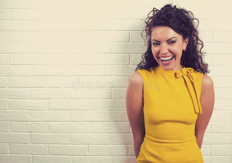 Muchacha feliz que ríe contra un fondo blanco de la pared de ladrillo imagen de archivo libre de regalías