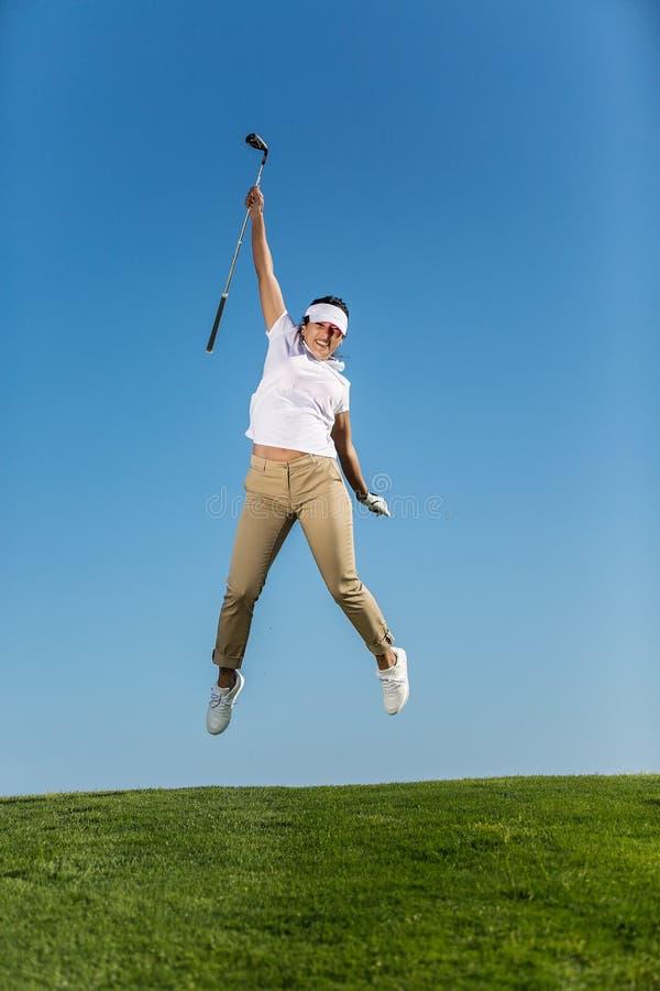 Muchacha feliz que salta arriba en campo de golf imagenes de archivo