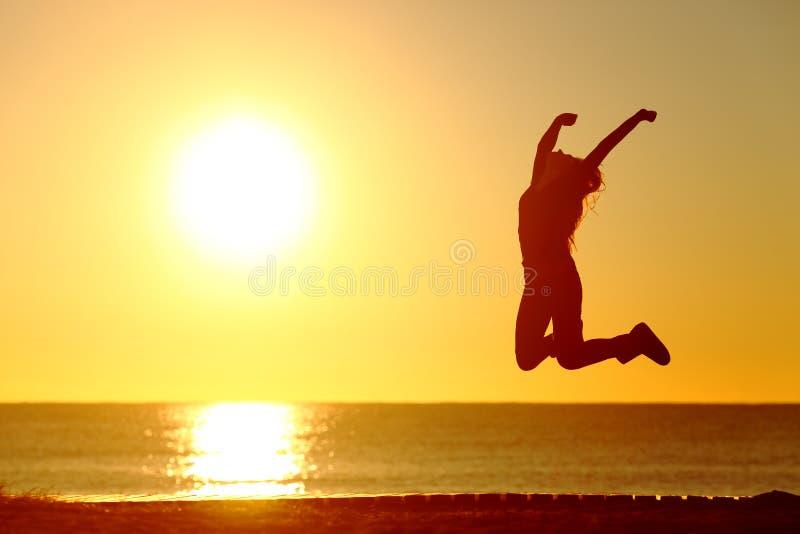 Muchacha feliz que salta en la playa en la puesta del sol fotografía de archivo