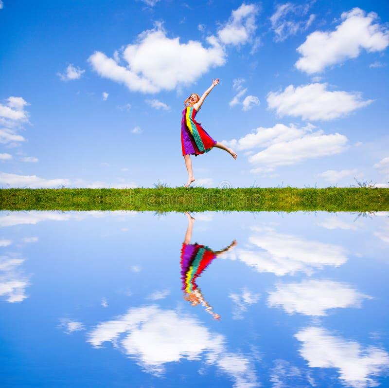 Muchacha feliz que salta junto en prado verde imagenes de archivo