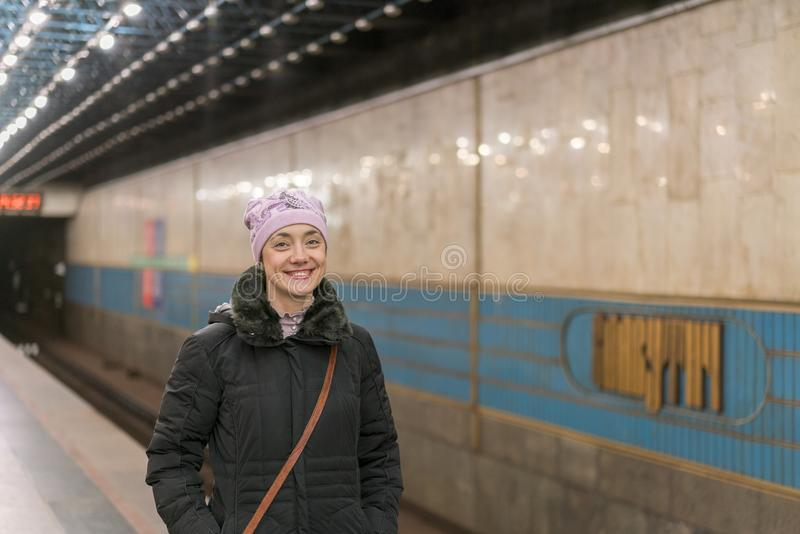 Muchacha feliz que se coloca en la plataforma del subterráneo fotos de archivo libres de regalías