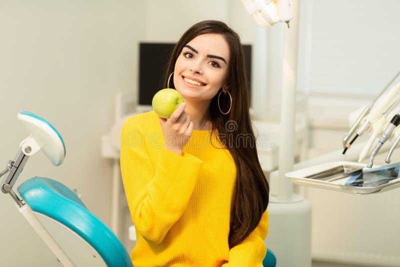 Muchacha feliz que se sienta en silla dental y que muestra manzanas frescas después del tratamiento dental acertado fotos de archivo libres de regalías