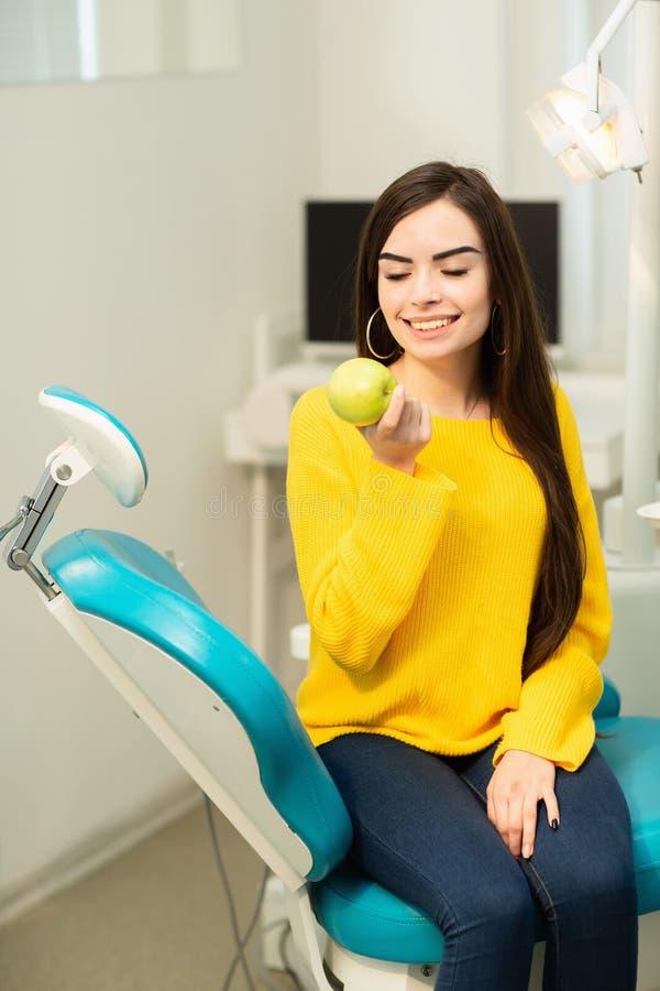 Muchacha feliz que se sienta en silla dental y que muestra manzanas frescas despu?s del tratamiento dental acertado foto de archivo