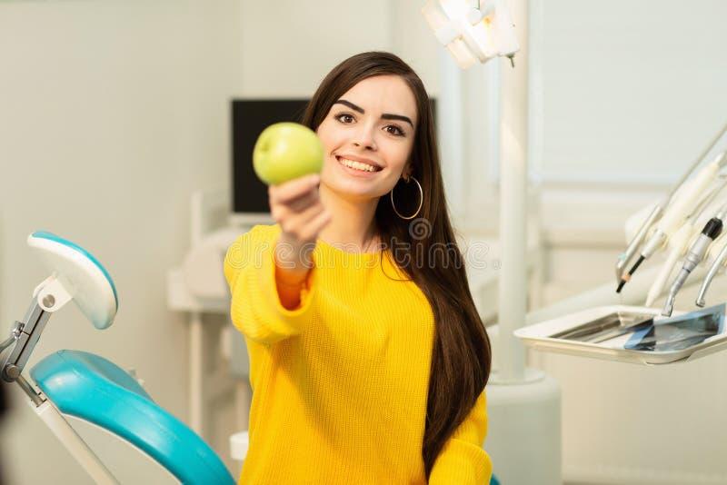 Muchacha feliz que se sienta en silla dental y que muestra manzanas frescas despu?s del tratamiento dental acertado imágenes de archivo libres de regalías