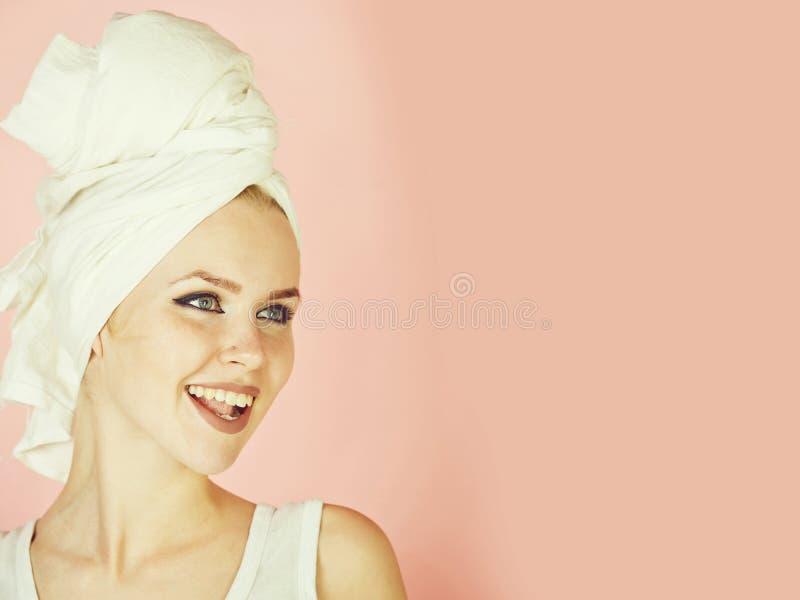 Muchacha feliz que sonríe con la toalla de baño blanca en la cabeza fotografía de archivo libre de regalías
