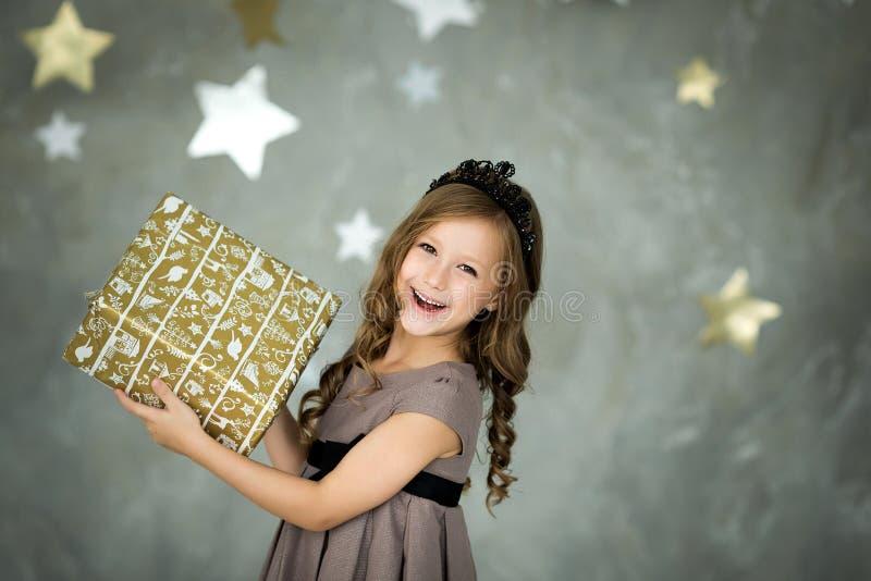 Muchacha feliz que sostiene la caja con los regalos concepto de la Navidad y de la gente imagen de archivo