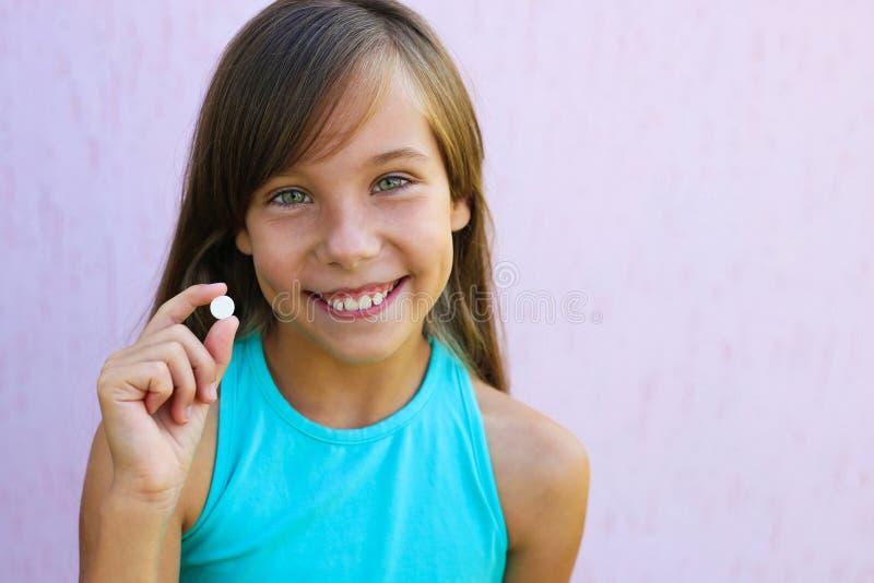 Muchacha feliz que sostiene la píldora disponible fotos de archivo libres de regalías