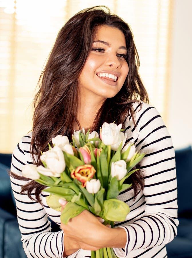 Muchacha feliz que sostiene las flores imagen de archivo