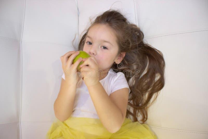 Muchacha feliz que sostiene y que come la pera dulce amarilla imagen de archivo libre de regalías