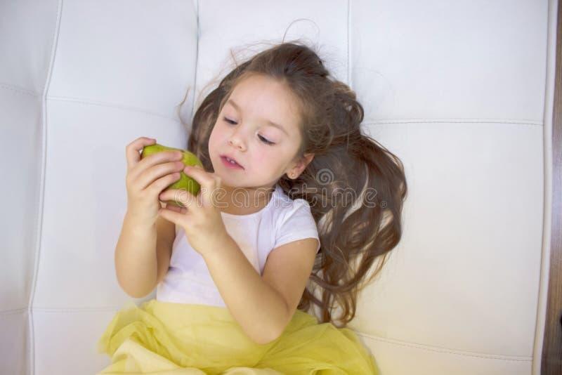 Muchacha feliz que sostiene y que come la pera dulce amarilla fotos de archivo