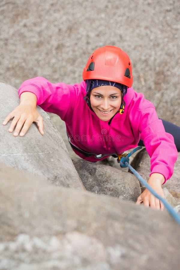 Muchacha feliz que sube para arriba la cara de la roca fotografía de archivo