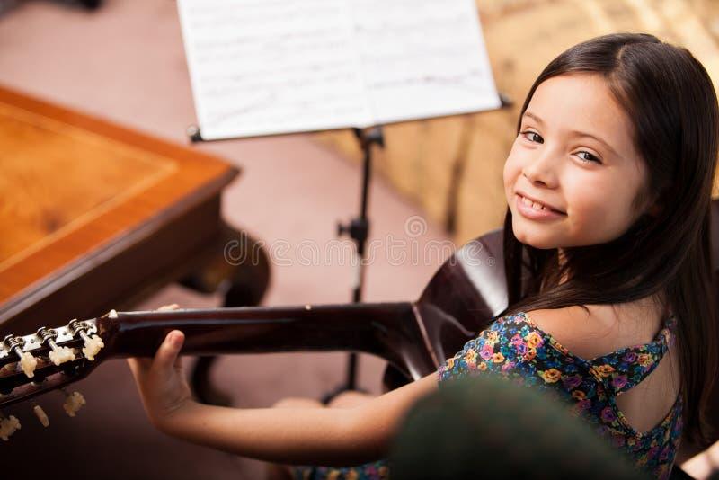 Muchacha feliz que toca la guitarra fotografía de archivo