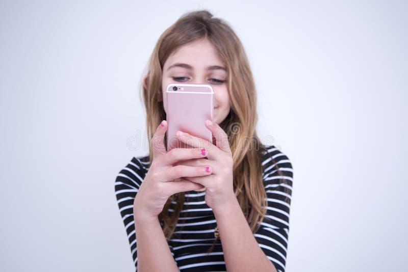 Muchacha feliz que usa su smartphone imagen de archivo