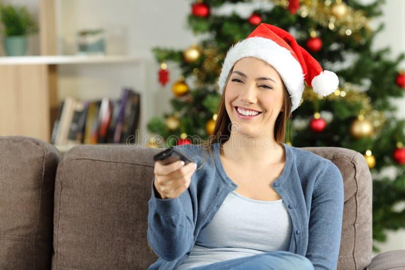 Muchacha feliz que ve la TV en casa en la Navidad imágenes de archivo libres de regalías