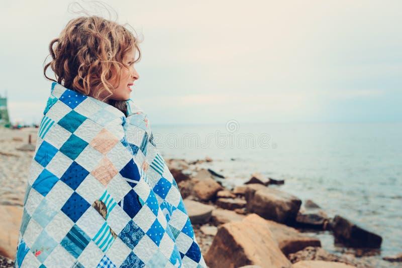 Muchacha feliz rizada linda del niño que se relaja en la playa de piedra, envuelta en manta acogedora del edredón imagen de archivo