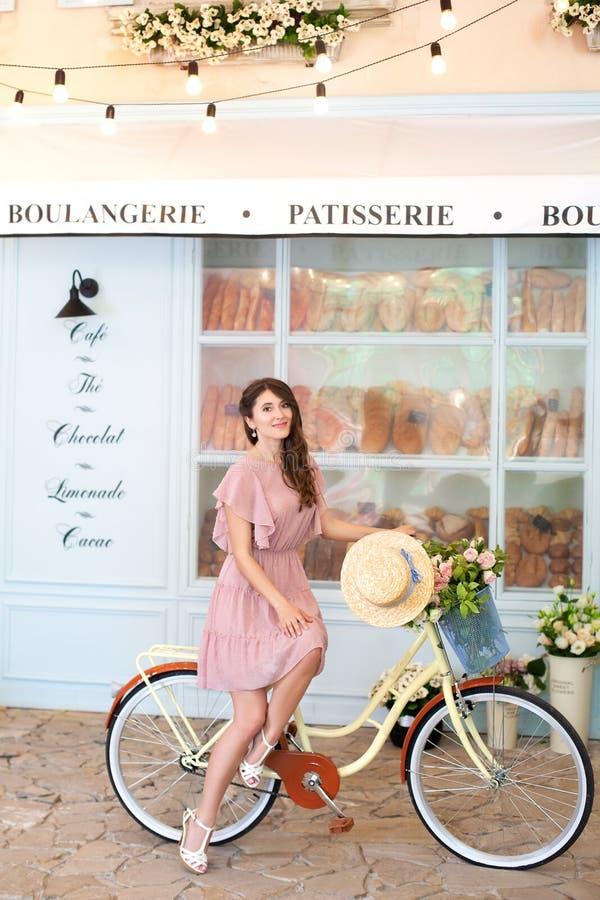 Muchacha feliz sonriente en bicicleta retra del montar a caballo del vestido y del sombrero en una calle de la ciudad Gente activ fotografía de archivo libre de regalías