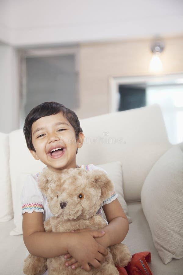 Muchacha feliz, sonriente que sostiene un oso de peluche y que se sienta en el sofá, mirando la cámara imagen de archivo