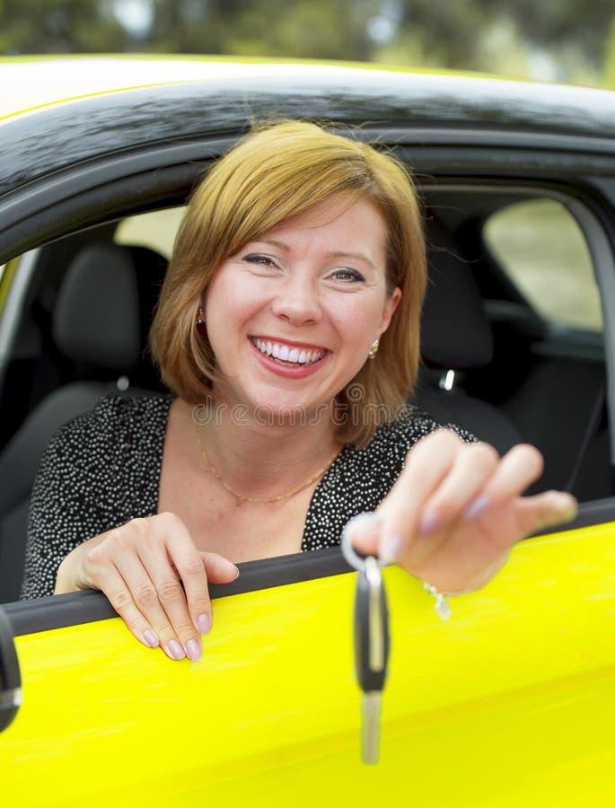 Muchacha feliz y sonriente del pelo rojo en su sentarse 20s o 30s orgulloso en el asiento de conductor que lleva a cabo y que mue fotos de archivo