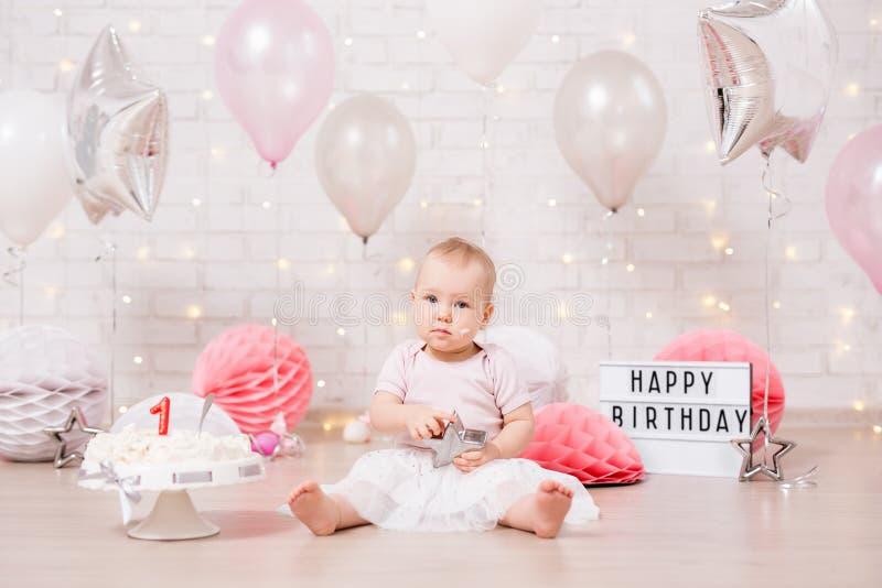 Muchacha feliz y torta de cumpleaños rota sobre la pared de ladrillo con las luces y los globos fotos de archivo