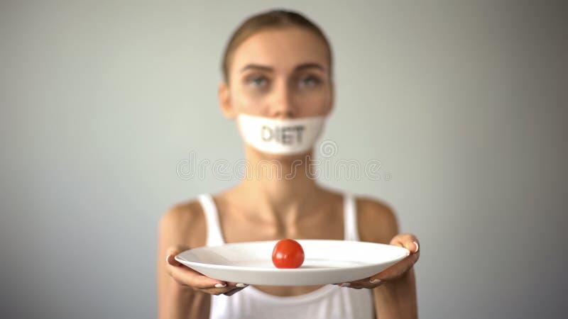 Muchacha fina con la placa grabada de la tenencia de la boca con el tomate, dieta de agotamiento, anorexia imagen de archivo