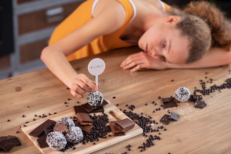 Muchacha flaca agradable que se inclina en la tabla de madera con el chocolate en él imagen de archivo libre de regalías