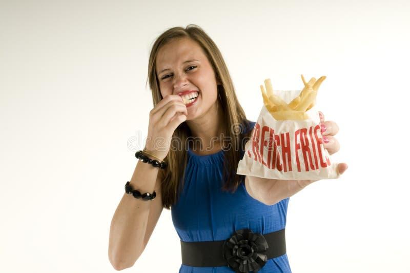Muchacha flaca que come las patatas fritas fotografía de archivo