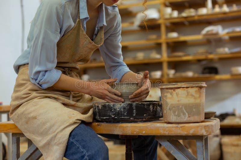 Muchacha flaca trabajadora que muestra su experiencia en cerámica fotografía de archivo
