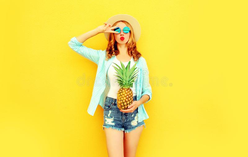 muchacha fresca con la piña que sopla los labios rojos que envían beso dulce del aire en el sombrero de paja del verano, gafas de fotos de archivo