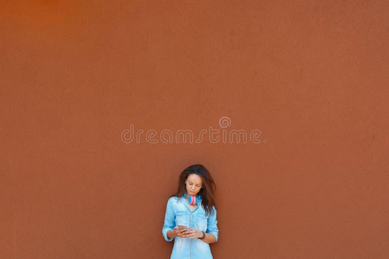 Muchacha fresca de moda en auriculares que escucha la música en el teléfono contra la perspectiva de la pared de la ciudad concep foto de archivo