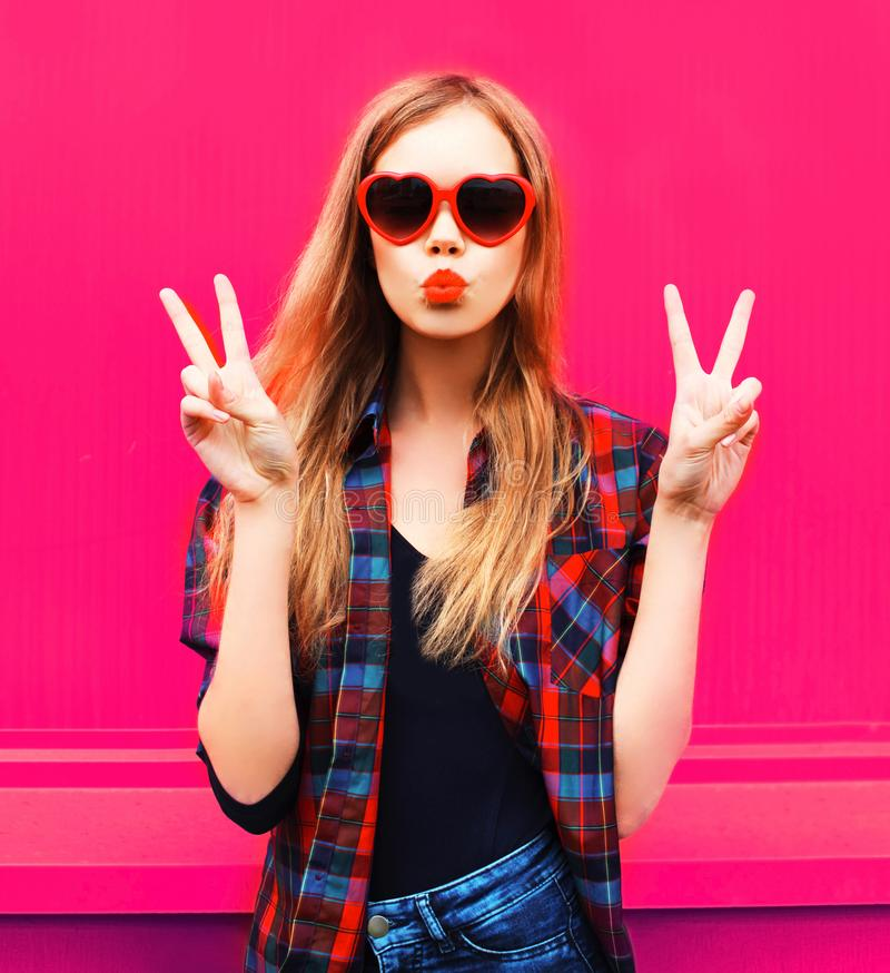 Muchacha fresca del retrato en las gafas de sol en forma de corazón que envían beso dulce del aire en rosa colorido foto de archivo libre de regalías