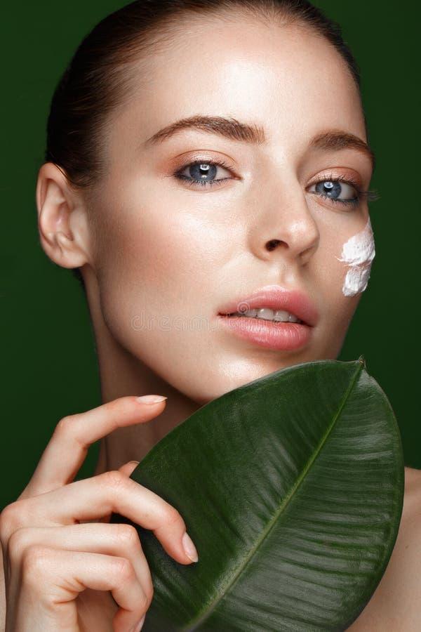 Muchacha fresca hermosa con crema cosmética en la cara, el maquillaje natural y las hojas del verde Cara de la belleza foto de archivo libre de regalías