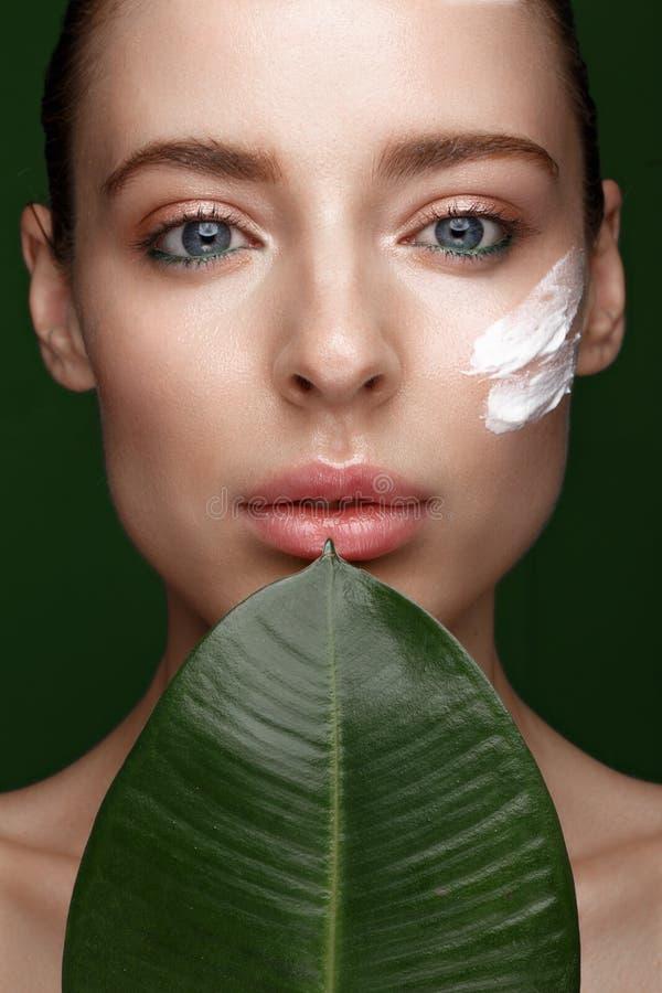Muchacha fresca hermosa con crema cosmética en la cara, el maquillaje natural y las hojas del verde Cara de la belleza imagen de archivo