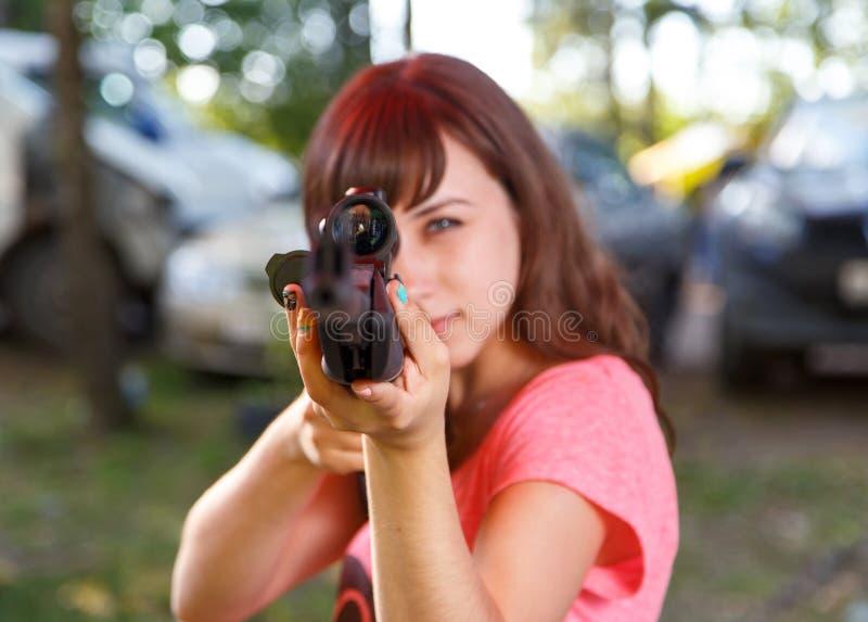 Muchacha fresca que apunta del rifle telescópico, foco en vista foto de archivo libre de regalías