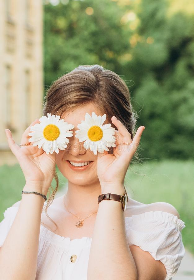 muchacha fuera de la flor de la manzanilla de campo que juega verano de la alegría fotos de archivo libres de regalías