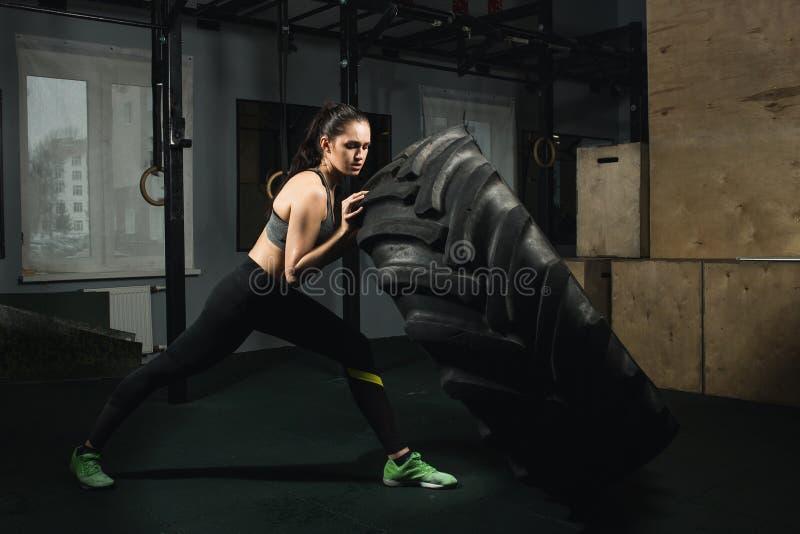 Muchacha fuerte que mueve de un tirón un neumático en gimnasio fotografía de archivo