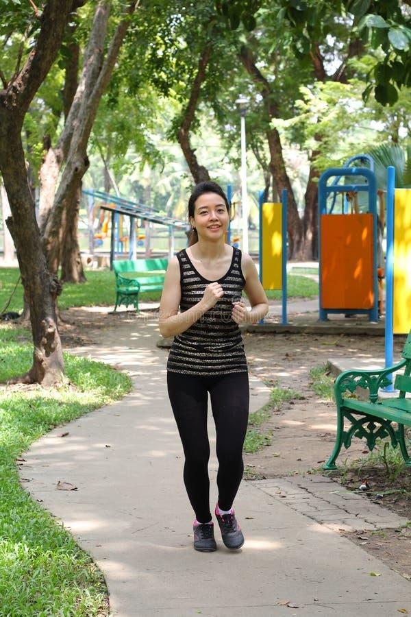 Muchacha hermosa adulta tailandesa que hace ejercicios corrientes en el parque imagen de archivo