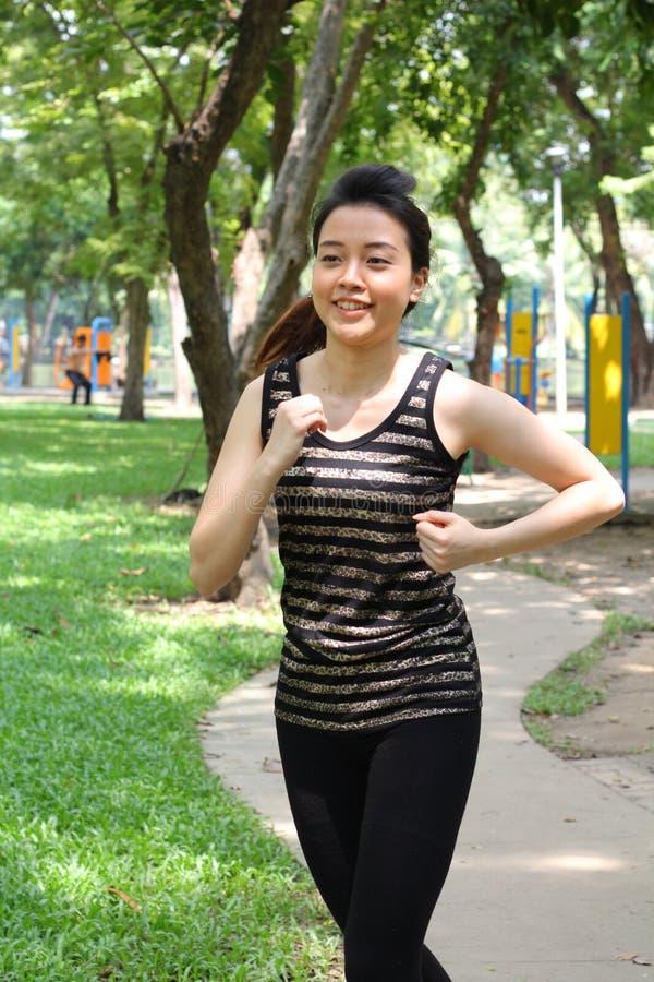 Muchacha hermosa adulta tailandesa que hace ejercicios corrientes en el parque foto de archivo libre de regalías