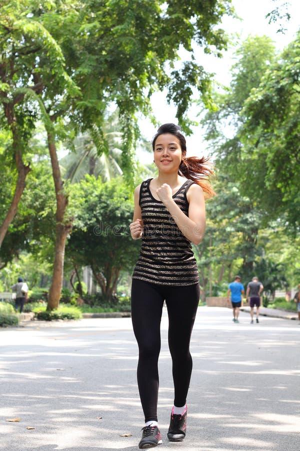 Muchacha hermosa adulta tailandesa que hace ejercicios corrientes en el parque fotos de archivo