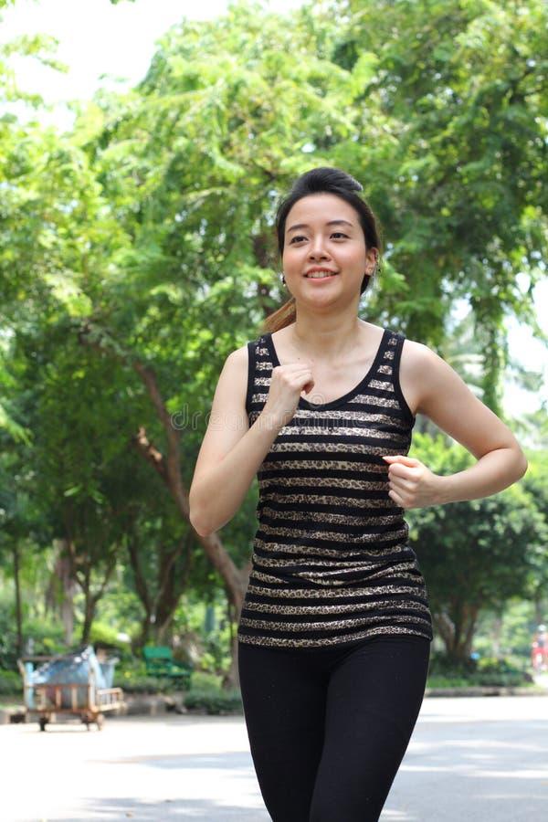 Muchacha hermosa adulta tailandesa que hace ejercicios corrientes en el parque foto de archivo