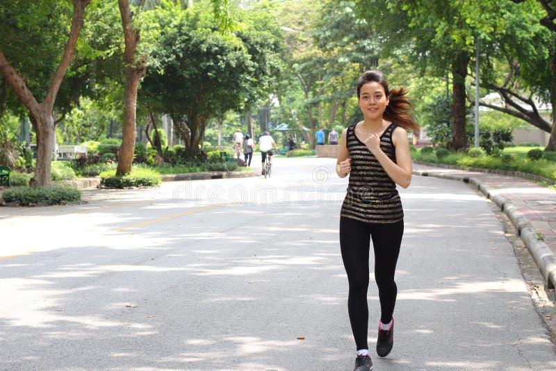 Muchacha hermosa adulta tailandesa que hace ejercicios corrientes en el parque imágenes de archivo libres de regalías