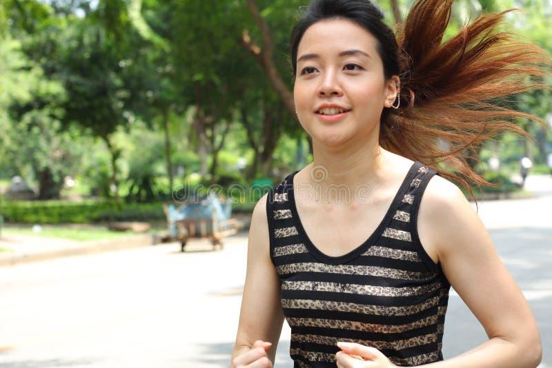 Muchacha hermosa adulta tailandesa que hace ejercicios corrientes en el parque fotos de archivo libres de regalías