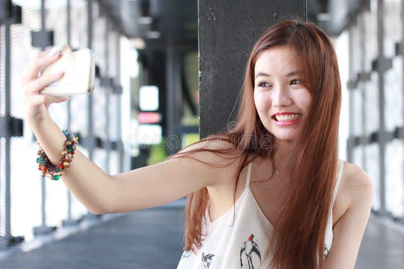 Muchacha hermosa adulta tailandesa que usa su teléfono elegante Selfie imagen de archivo