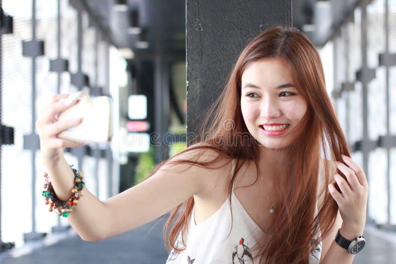 Muchacha hermosa adulta tailandesa que usa su teléfono elegante Selfie fotos de archivo