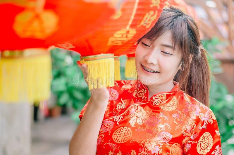 Muchacha hermosa asiática joven en soporte rojo tradicional chino de la sonrisa del vestido cerca de la lámpara de China, en el A imagenes de archivo
