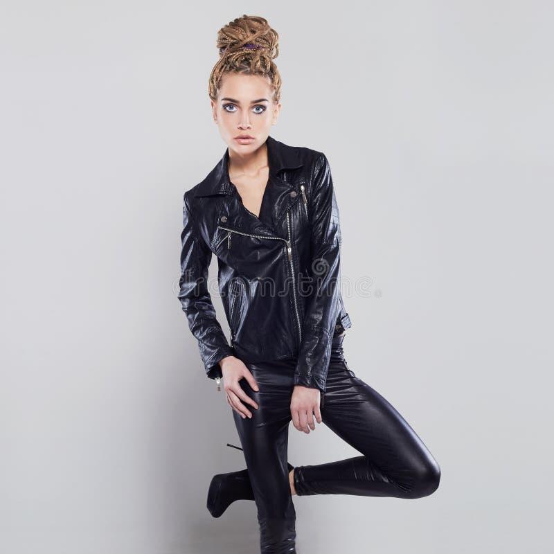 Muchacha hermosa atractiva en cuero mujer joven rubia del punk rock en látex imagen de archivo