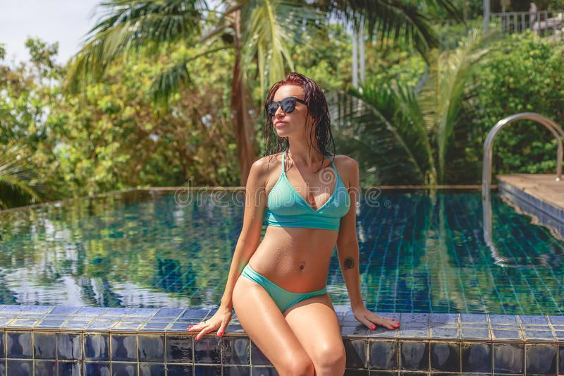 muchacha hermosa atractiva en sentarse del bikini imagen de archivo