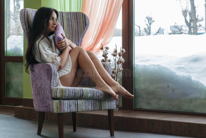 Muchacha hermosa cerca de la ventana por la mañana imagen de archivo libre de regalías