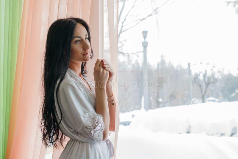 Muchacha hermosa cerca de la ventana por la mañana fotos de archivo