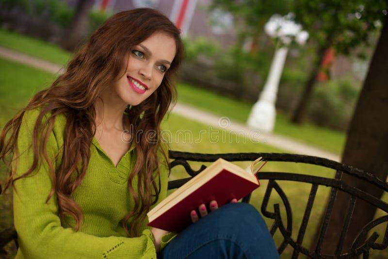 Muchacha hermosa con el libro en el parque fotografía de archivo libre de regalías